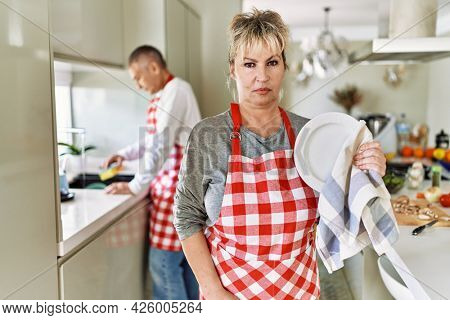 Middle age caucasian couple wearing apron washing dishes at home thinking attitude and sober expression looking self confident