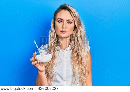 Beautiful young blonde woman holding bowl with sugar thinking attitude and sober expression looking self confident