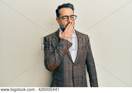 Middle age man with beard and grey hair wearing business jacket and glasses bored yawning tired covering mouth with hand. restless and sleepiness.