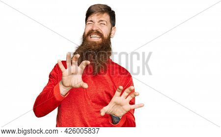 Redhead man with long beard wearing casual clothes disgusted expression, displeased and fearful doing disgust face because aversion reaction. with hands raised