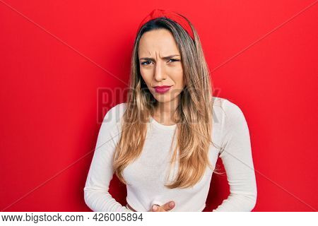 Beautiful hispanic woman wearing red diadem with hand on stomach because indigestion, painful illness feeling unwell. ache concept.