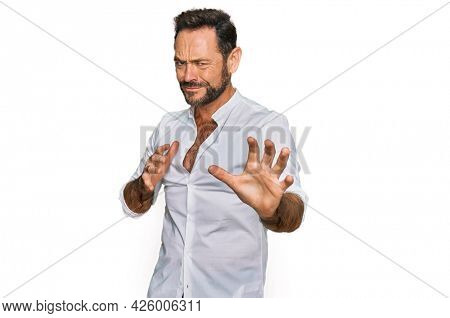 Middle age man wearing casual clothes disgusted expression, displeased and fearful doing disgust face because aversion reaction. with hands raised