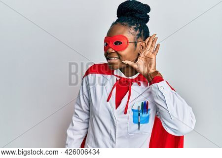 Young african american woman wearing doctor uniform and super hero costume smiling with hand over ear listening and hearing to rumor or gossip. deafness concept.