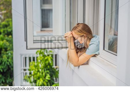 Extremly Tired Woman Looking Out The Window, Home Alone. Self-isolation At Home, Quarantine Due To P
