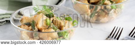 Narrow View Of A Bowl Of A Potato Salad With Another In Soft Focus In Behind.