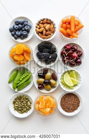 Many Various Fresh Organic Ingredients In Small Dishes Against A Bright White Background.