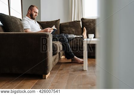 White man with prosthesis reading book while siting on couch at home