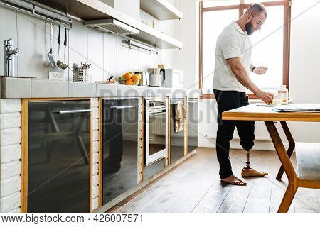 White man with prosthesis taking her medicine while standing at kitchen
