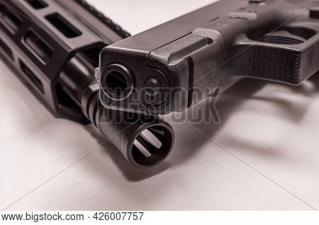 A Black 9mm Pistol On Top Of A Black Ar 15 .223 Caliber Rifle With A White Background