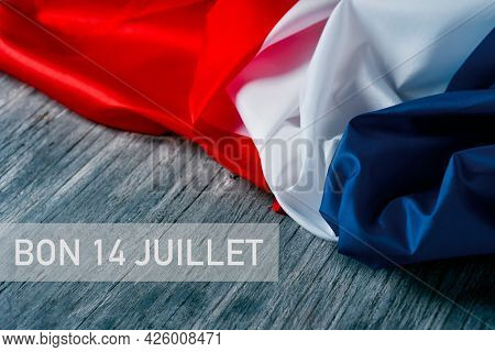 the text bon 14 juillet, happy 14 july, the national day of france written in french, and a french flag on a gray rustic wooden background