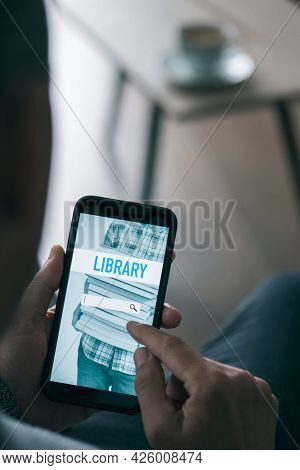 a young man, sitting at a coffee table in his living room, is searching an ebook to lend on an online library with his smartphone, with a simulated search engine in its screen