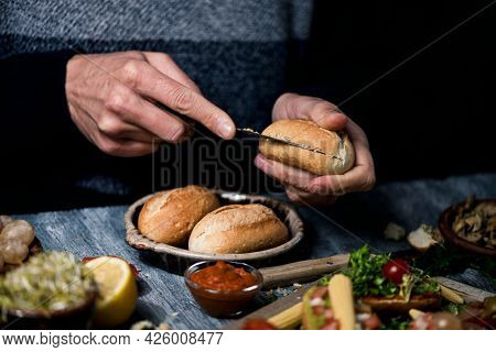 closeup of a young caucasian man cutting a bread bun to prepare a sandwich or some vegan snacks, sitting at a gray wooden table, to a tray with some vegan appetizers