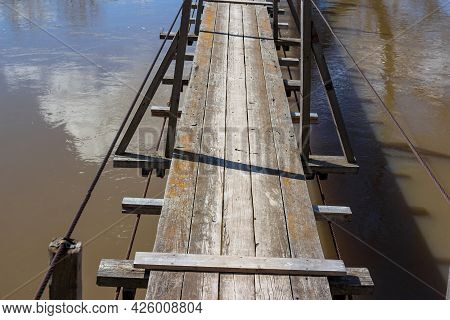 Suspended Pedestrian Bridge Over The River With Wooden Deck