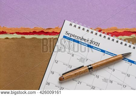 September 2021 - spiral desktop calendar against colorful abstract paper landscape with a stylish pen, time and business concept