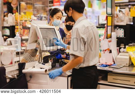Male Cashier Staff With Blue Glove Working At Checkout Counter