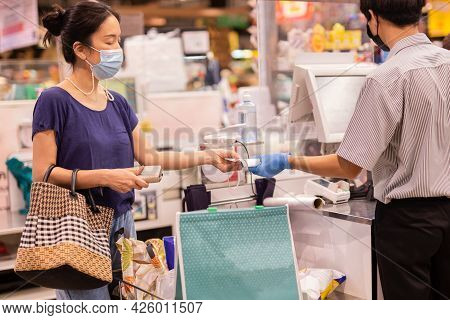 Woman With Medical Mask Taking Receipt From Male Cashier At Supermarket