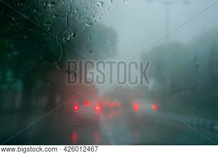 Red Backlight Of Cars. Image Shot Through Raindrops Falling On Wet Glass, Abstract Blurs Of Traffic
