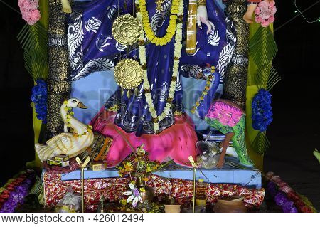 Ducks Beside The Legs Of Idol Of Goddess Saraswati Being Worshipped At Night. Colorful Light On Hind