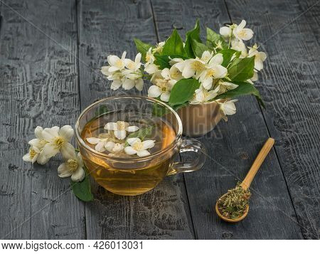 Jasmine Flowers And Flower Tea In A Glass Bowl On A Wooden Table. An Invigorating Drink That Is Good