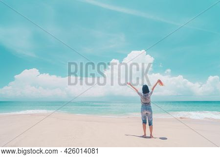 Happy Woman Raise Hand Up At Tropical Beach With Blue Sky Background. Travel Vacation And Freedom Fe