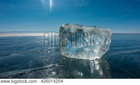 A Transparent Ice Crystal Lies On The Smooth Blue Surface Of A Frozen Lake. Glare Of The Sun On The