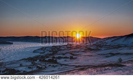 Winter Sunrise Over The Siberian Valley. The Sun's Rays Paint The Sky Over The Ridge Orange. Glare O