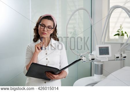 Cosmetologist Thinking And Standing In Cosmetology Clinic, Filling Out Papers With Medical Records W