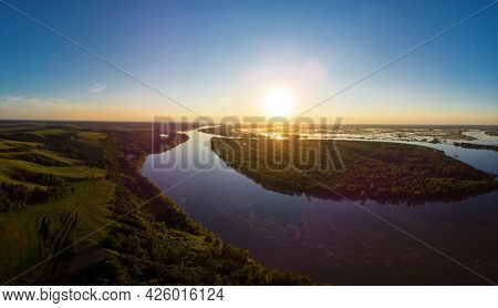 Aerial drone view of river landscape in sunny summer sunset. Top view of siberian Ob river from high attitude in summer sunset. Panorama, bird's eye view