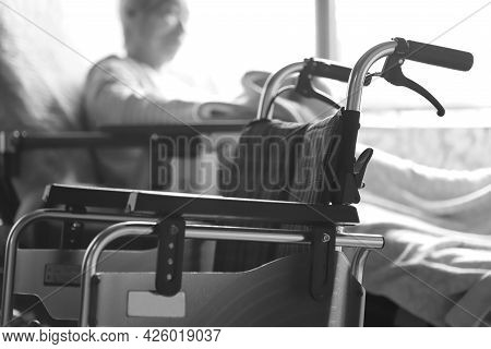 Elderly Woman With Dementia Playing With A Blanket While Relaxing In A Nursing Bed