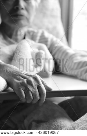 Elderly Woman With Dementia Holding On To A Table While Relaxing In A Nursing Bed