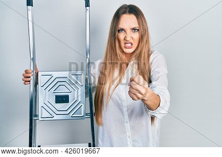 Young blonde girl holding ladder annoyed and frustrated shouting with anger, yelling crazy with anger and hand raised