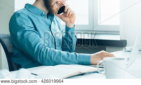 Faceless Smiling Busy Man Entrepreneur In Casual Clothes Talking On Mobile Phone And Looking At Lapt
