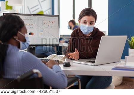 Company Manager With Mask Against Coronavirus Explaining To African Paralysed Colleague Project Plan