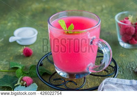 Traditional Russian Hot Drink Raspberry Jelly Or Kissel In A Glass Transparent Mug On A Green Concre