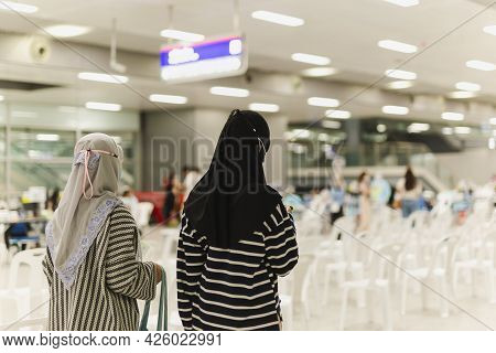Muslim Student Walking In Building With Friend.