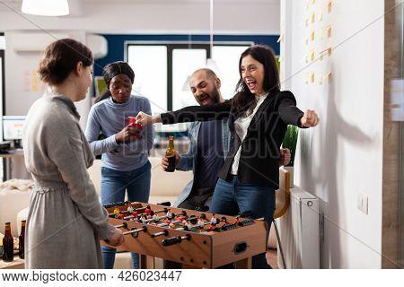 Cheerful Team Of Multi Ethnic Colleagues Enjoy Foosball Table Game Football Soccer. Happy Woman Winn