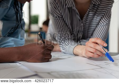 Close Up Of Diverse Architect Women Hands Working On Blueprint Plans At Desk. Professional Engineer