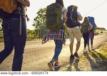 Young Travelers Hikers Hiking And Hitch-hiking On Road With Backpacks Together During Summer Vacatio