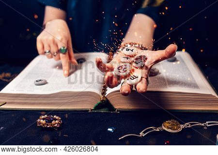 Fortune Teller's Hand Holds The Sparkling Zodiac Stones In The Palm Of Her Hand Over The Open Book.