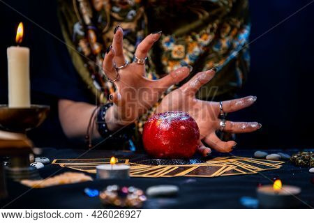 A Fortune Teller Conjures A Red Apple Lying On The Tarot Cards. On The Table Is A Lighted Candle And