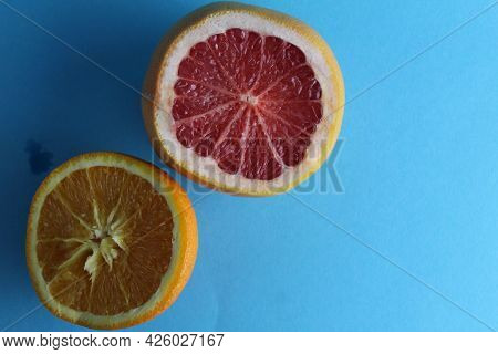 Half Of Grapefruit And Orange On A Blue Background. View From Above Flatley