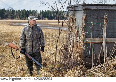 A Duck Hunter Stands Next To An Old Hunting Shelter. He Has A Shotgun In His Hands. Behind The Hunte