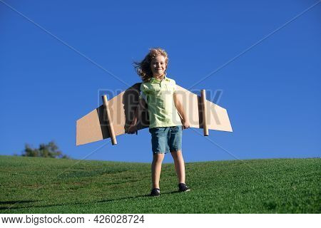 Child Playing With Cardboard Toy Wings In The Park. Concept Of Children Day. Kid Boy In An Pilot Cos