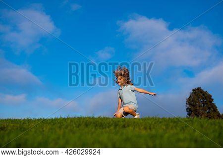 Kid Running On Grass Field. Cute Boy Run In Summer Park. Child Running On Meadow.