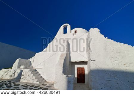 Famous Tourist Landmark, Mykonos, Greece. White Greek Orthodox Church Of Panagia Paraportiani, Town