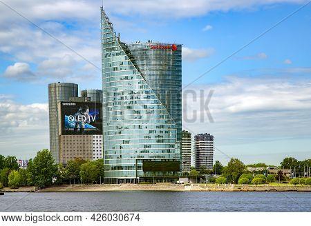 Latvia, Riga, May, 2021 - Modern Glass Skyscraper Of Swedbank Office On The Embankment Of The Daugav