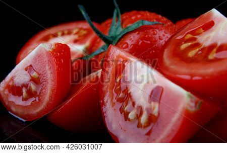 Pieces Of Cut Tomato On A Black Background.