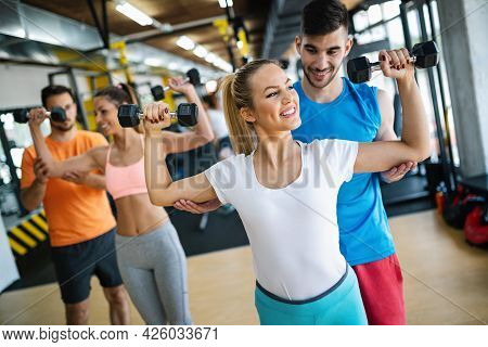Group Of Fit Young People Exercising At The Gym