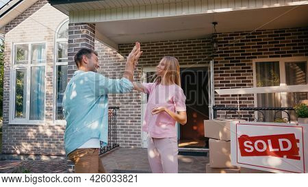 Happy Couple Giving High Five Near New House And Sold Board.