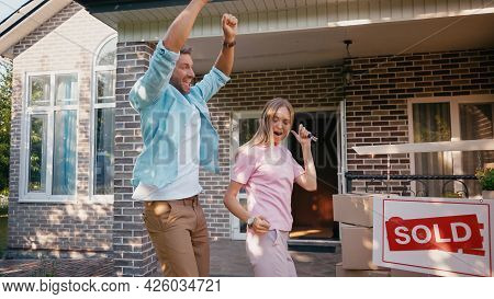 Happy Man Holding Keys Near Wife And Dancing Near New House And Sold Board.
